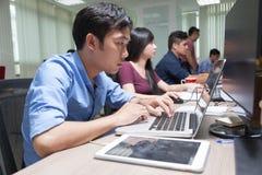Ασιατική συνεδρίαση επιχειρηματιών στη λειτουργώντας επιχείρηση φορητών προσωπικών υπολογιστών γραφείων Στοκ Φωτογραφία