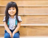 Ασιατική συνεδρίαση χαμόγελου κοριτσιών στην κίτρινη γραμμή σκαλοπατιών Στοκ εικόνα με δικαίωμα ελεύθερης χρήσης