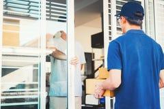 Ασιατική υπηρεσία παράδοσης ατόμων με τα κιβώτια στα χέρια που στέκονται μπροστά από τις πόρτες σπιτιών του πελάτη στοκ εικόνες