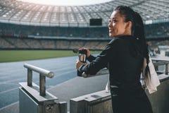 Ασιατική φίλαθλος με το αθλητικό μπουκάλι και πετσέτα στο στάδιο Στοκ φωτογραφίες με δικαίωμα ελεύθερης χρήσης