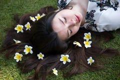 Ασιατική όμορφη νέα γυναίκα που βρίσκεται στο χορτοτάπητα με τα λουλούδια στοκ φωτογραφίες