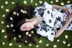 Ασιατική όμορφη νέα γυναίκα που βρίσκεται στο χορτοτάπητα με τα λουλούδια στοκ εικόνες