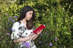 Ασιατική όμορφη νέα γυναίκα που διαβάζει ένα βιβλίο στον υπαίθριο κήπο στοκ εικόνες