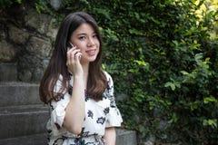 Ασιατική όμορφη νέα γυναίκα που μιλά στο τηλέφωνο στοκ εικόνες