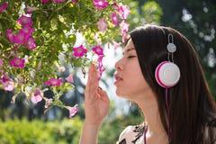 Ασιατική όμορφη νέα γυναίκα που φορά τα ακουστικά στον κήπο στοκ φωτογραφία