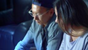 Ασιατική όμορφη νέα συνεδρίαση ζευγών στον καναπέ με τον υπολογιστή ταμπλετών στο δωμάτιο το βράδυ απόθεμα βίντεο