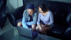 Ασιατική όμορφη νέα συνεδρίαση ζευγών στον καναπέ με τον υπολογιστή ταμπλετών στο δωμάτιο το βράδυ φιλμ μικρού μήκους