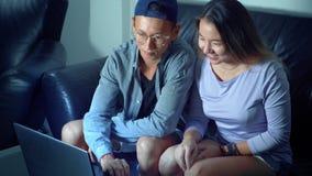Ασιατική όμορφη νέα συνεδρίαση ζευγών στον καναπέ με τον υπολογιστή ταμπλετών στο δωμάτιο το βράδυ στοκ εικόνες