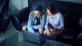 Ασιατική όμορφη νέα συνεδρίαση ζευγών στον καναπέ με τον υπολογιστή ταμπλετών στο δωμάτιο το βράδυ στοκ φωτογραφίες με δικαίωμα ελεύθερης χρήσης