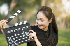 Ασιατική clapper εκμετάλλευσης κοριτσιών επιτροπή στα χέρια της στοκ εικόνες