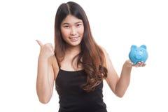 Ασιατικοί αντίχειρες γυναικών επάνω με την τράπεζα νομισμάτων χοίρων Στοκ Εικόνες