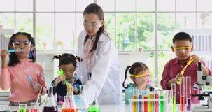 Ασιατικοί δάσκαλος και σπουδαστές που φυσούν τις φυσαλίδες στο εργαστήριο απόθεμα βίντεο