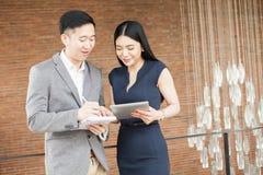 Ασιατικοί επιχειρηματίας και επιχειρησιακή γυναίκα που έχουν μια περιστασιακή επιχειρησιακή συνομιλία Στοκ Εικόνες