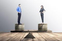 Ασιατικοί επιχειρηματίας και επιχειρηματίας που στέκονται στο σωρό νομισμάτων με το ίδιο ύψος balancer στοκ εικόνες