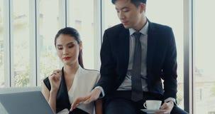 Ασιατικοί επιχειρηματίες που χρησιμοποιούν το lap-top στην αρχή απόθεμα βίντεο