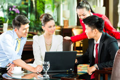 Ασιατικοί επιχειρηματίες στη συνεδρίαση στο λόμπι ξενοδοχείων Στοκ Εικόνα