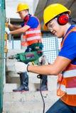 Ασιατικοί εργάτες οικοδομών που τρυπούν με τρυπάνι στην οικοδόμηση των τοίχων Στοκ φωτογραφία με δικαίωμα ελεύθερης χρήσης