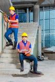 Ασιατικοί εργαζόμενοι στην οικοδόμηση ή τον τοίχο εργοτάξιων οικοδομής Στοκ Εικόνες