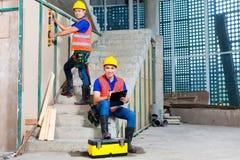 Ασιατικοί εργαζόμενοι στην οικοδόμηση ή τον τοίχο εργοτάξιων οικοδομής Στοκ Φωτογραφία