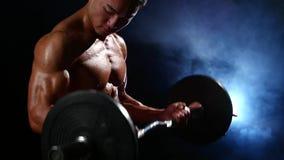 Ασιατικοί δικέφαλοι μυ'ες κατάρτισης bodybuilder με ένα barbell Μαύρο υπόβαθρο καπνού κίνηση αργή απόθεμα βίντεο