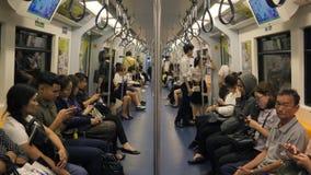Ασιατικοί λαοί που χρησιμοποιούν τα έξυπνες τηλέφωνα και τις συσκευές μέσα στο βαγόνι εμπορευμάτων υπόγειων τρένων BTS 4K Μπανγκό απόθεμα βίντεο