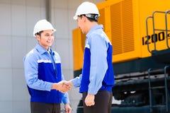 Ασιατικοί μηχανικοί που έχουν τη συμφωνία για το εργοτάξιο οικοδομής Στοκ Φωτογραφίες