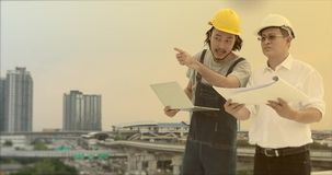 Ασιατικοί μηχανικοί που στέκονται στη στέγη, το νέο χρησιμοποιώντας σημειωματάριο για να εξηγήσει την εργασία του στον παλαιό, φιλμ μικρού μήκους