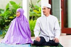 Ασιατικοί μουσουλμανικοί ζεύγος, άνδρας και γυναίκα, που προσεύχονται στο σπίτι Στοκ εικόνες με δικαίωμα ελεύθερης χρήσης