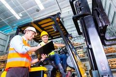 Ασιατικοί οδηγός φορτηγού και επιστάτης ανελκυστήρων στην αποθήκευση Στοκ φωτογραφίες με δικαίωμα ελεύθερης χρήσης
