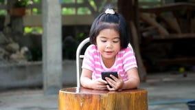Ασιατικοί παίζοντας αγώνες κοριτσιών στο έξυπνο τηλέφωνο χαρωπά απόθεμα βίντεο