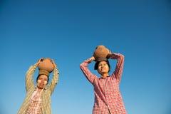 Ασιατικοί παραδοσιακοί αγρότες που φέρνουν το δοχείο στο κεφάλι Στοκ Φωτογραφίες