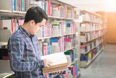 Ασιατικός άνδρας σπουδαστής που διαβάζει ένα βιβλίο σε μια βιβλιοθήκη, γνώση, educa Στοκ Εικόνες