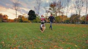 Ασιατικός άνδρας και καυκάσια γυναίκα που τρέχουν στο πάρκο με το σκυλί του Ευτυχής μαζί, γέλιο απόθεμα βίντεο