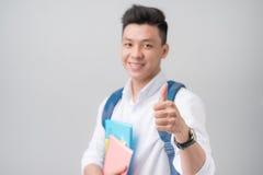 Ασιατικός άνδρας σπουδαστής που καθιστά ένα σημάδι αντίχειρων επάνω απομονωμένο στην άσπρη πλάτη Στοκ φωτογραφία με δικαίωμα ελεύθερης χρήσης