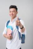 Ασιατικός άνδρας σπουδαστής που καθιστά ένα σημάδι αντίχειρων επάνω απομονωμένο στην άσπρη πλάτη Στοκ Φωτογραφίες