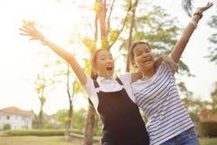 Ασιατικός έφηβος δύο που γελά με τη συγκίνηση ευτυχίας στο πράσινο natu στοκ φωτογραφία