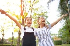 Ασιατικός έφηβος δύο που γελά με τη συγκίνηση ευτυχίας στο πράσινο natu στοκ φωτογραφίες με δικαίωμα ελεύθερης χρήσης
