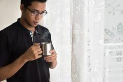 Ασιατικός έφηβος που κρατά μια κούπα με τα καυτά ποτά το πρωί Στοκ Φωτογραφία