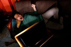 Ασιατικός έφηβος που τρυπιούνται και βίντεο προσοχής σε ένα lap-top Στοκ φωτογραφία με δικαίωμα ελεύθερης χρήσης