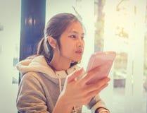 Ασιατικός έφηβος που χρησιμοποιεί το κινητό τηλέφωνο Στοκ Φωτογραφίες