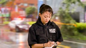 Ασιατικός αμερικανικός αστυνομικός στη σκηνή εγκλήματος που παίρνει τις σημειώσεις στοκ φωτογραφία