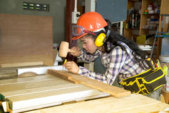 Ασιατικός αρκετά θηλυκός ξυλουργός που χρησιμοποιεί το ξύλινο σφυρί Στοκ εικόνα με δικαίωμα ελεύθερης χρήσης