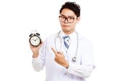 Ασιατικός αρσενικός γιατρός με το σοβαρό σημείο προσώπου σε ένα ρολόι Στοκ εικόνα με δικαίωμα ελεύθερης χρήσης