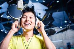 Ασιατικός αρσενικός τραγουδιστής που παράγει το τραγούδι στο στούντιο καταγραφής Στοκ Φωτογραφία