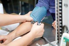 Ασιατικός αρσενικός χορηγός αίματος που μετρά τη πίεση του αίματος από το sphygmonometer υδραργύρου Στοκ Φωτογραφία
