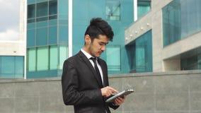 Ασιατικός εθνικός επιχειρηματίας που εργάζεται στην ταμπλέτα απόθεμα βίντεο