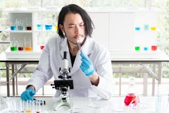 Ασιατικός επιστήμονας ή φαρμακοποιός που εξετάζει μια ταμπλέτα στο εργαστήριο, η ιατρική δοκιμής νεαρών άνδρων στο ιατρικό πείραμ στοκ εικόνα