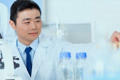 Ασιατικός επιστήμονας στο άσπρο λειτουργώντας εργαστήριο παλτών Στοκ Εικόνες