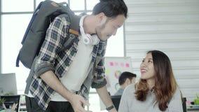 Ασιατικός επιχειρηματίας που δίνει τον καφέ στο συνάδελφό του που εργάζεται με το lap-top στο γραφείο απόθεμα βίντεο
