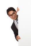 Ασιατικός επιχειρηματίας που κρυφοκοιτάζει από το πίσω κενό έμβλημα Στοκ φωτογραφίες με δικαίωμα ελεύθερης χρήσης
